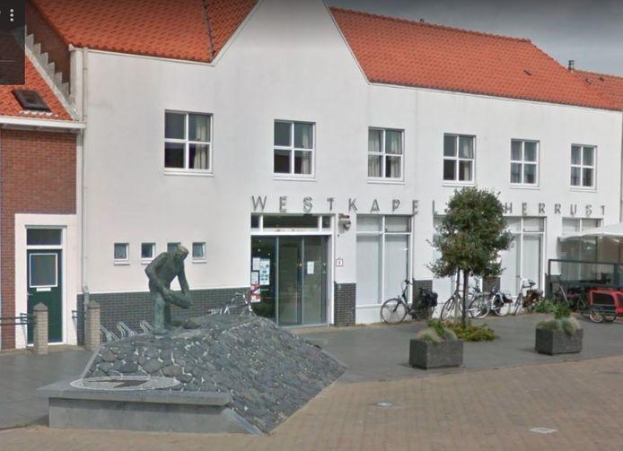 Het markante verenigingsgebouw Westkapelle Herrijst aan de Markt. Links het standbeeld voor de dijkwerker van kunstenaar Ad Braat.