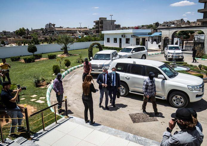 Koerdische beveiligers kijken toe als onder meer de Nederlandse gezant voor Syrië Emiel de Bont arriveert (links van de twee mannen in het midde).