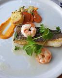 Op de huid gebakken kabeljauwfilet. Gezien de structuur en droge smaak, bestaat het vermoeden dat de vis uit de diepvries komt. Twee koude tijgergarnaaltjes, wat groenten en citrusvinaigrette kleden het bord aan.
