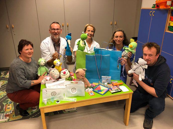 Joyce De Saeger (links) en Toon Verheijen (rechts) overhandigen de pakketten aan dokters en een verpleegkundige van de kinderafdeling in AZ Turnhout.