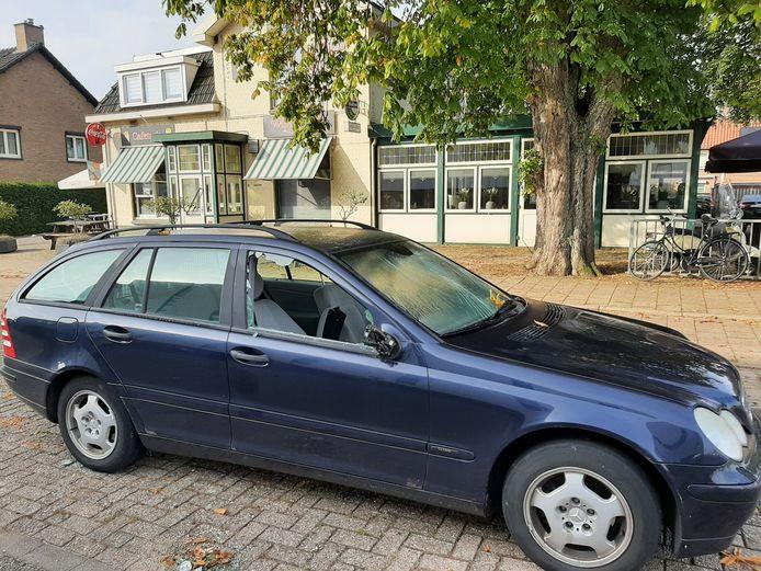 De geparkeerde auto voor cafe Wijnbergen in Doetinchem, met meerdere ingeslagen ruiten.