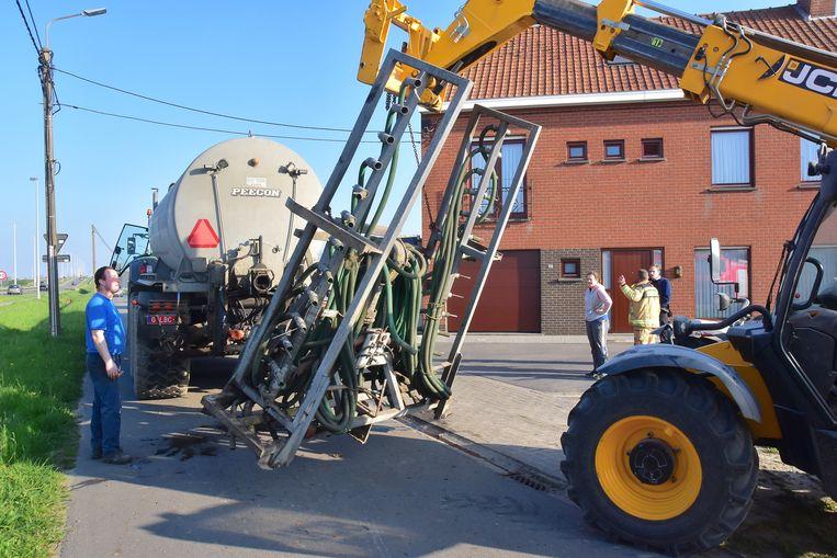 Met een verreiker werd de gehavende installatie om mest te injecteren van de aanhangwagen gehaald.