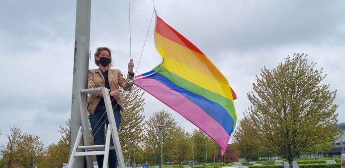 De burgemeester hijst de regenboogvlag.