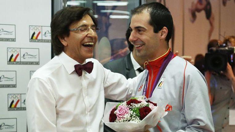 Cox, met bloemen in de hand, met premier Elio Di Rupo.