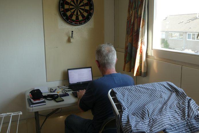 Verslaggever Domien van der Meijden zit tussen het wasgoed en onder het dartbord te werken.