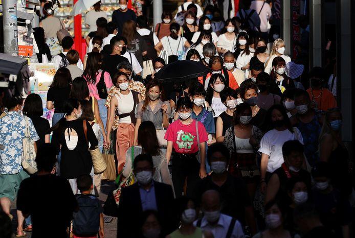 Des personnes portant des masques de protection, dans le cadre de l'épidémie de coronavirus (COVID-19), se dirigent vers un centre commercial à Tokyo, au Japon, le 5 août 2021.