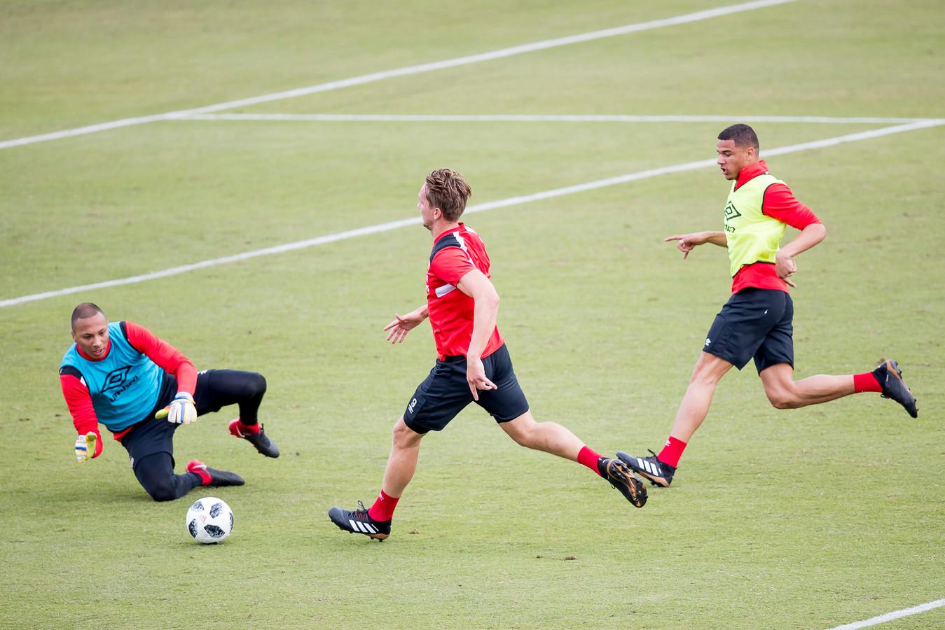 Armando Obispo (links) verdedigt bij PSV Luuk de Jong. Keeper Eloy Room grijpt in.