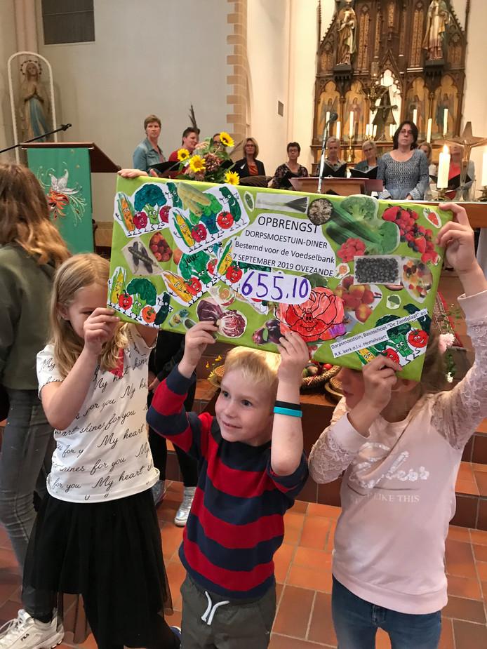 Kinderen presenteren de cheque met daarop de opbrengst van het Dorpsmoestuindiner.