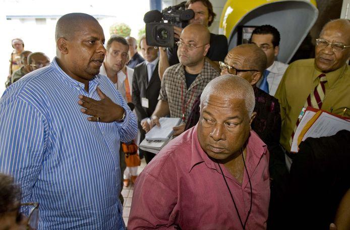 Etienne Boerenveen (links) en Eddie Daal (rood hemd), broer van slachtoffer Cyrill Daal, ontmoeten elkaar bij de ingang van de rechtbank op de marinebasis in het plaatsje Boxel, net buiten Paramaribo.