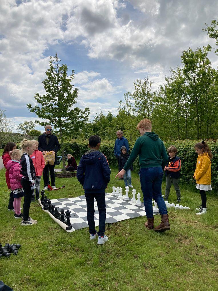 Tieners van de schaakclub helpen kinderen schaken in groepen in het Máximapark. Beeld