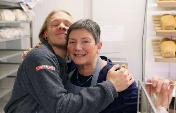 Werknemers Michaël en Annie geven elkaar een stevige knuffel.