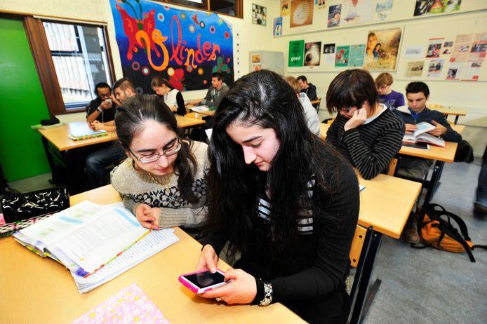 Een middelbare scholiere checkt haar mobieltje in de klas. Het smartphonegebruik kost leerlingen op een volle schooldag bijna een lesuur per dag aan verloren tijd.