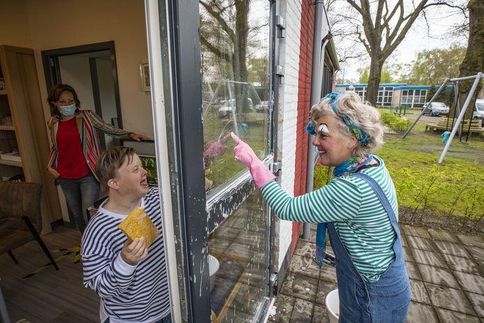 Raamzeemclown Lenneke van Asperen, hier aan het werk in Oldenzaal, heeft via het glas meteen contact met Aveleijncliënten die binnen zitten.