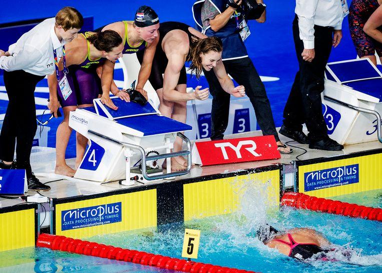 Kim Busch, Kira Toussaint en Femke Heemskerk (vlnr) aan de badrand gespannen in afwachting van de finish van Ranomi Kromowidjojo op de 4 x 100 meter vrije slag, tijdens het EK van 2018 in Glasgow. Het Nederlandse viertal won de zilveren medaille. Beeld ANP, Robin van Lonkhuijsen