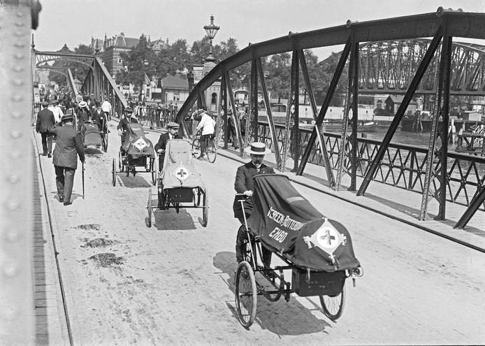 Fietsambulances op de Koninginnebrug, ruim een eeuw geleden. In de periode 1914-1918, toen de wereld werd geteisterd door de Eerste Wereldoorlog, waarin Nederland neutraal was.