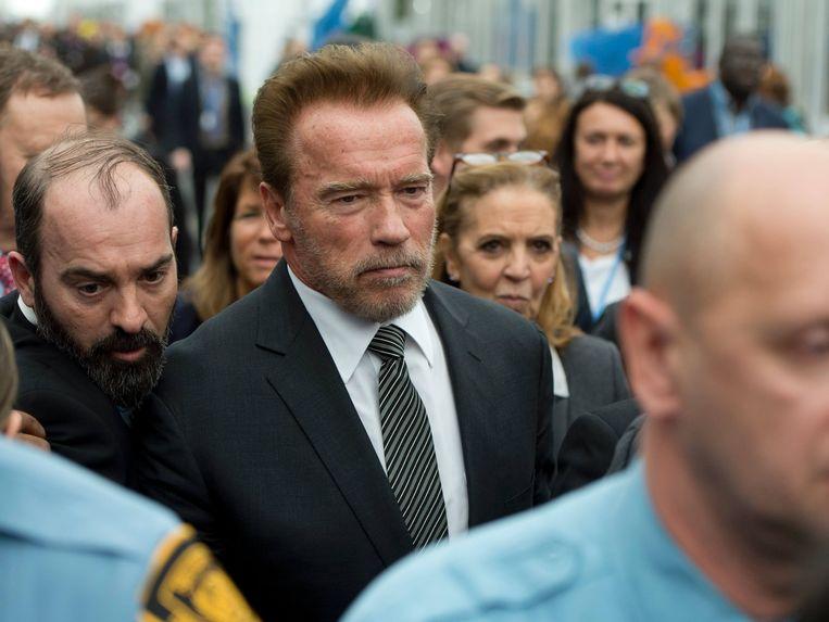 Arnold Schwarzenegger na zijn persconferentie tijdens de klimaattop in Parijs. Beeld AFP