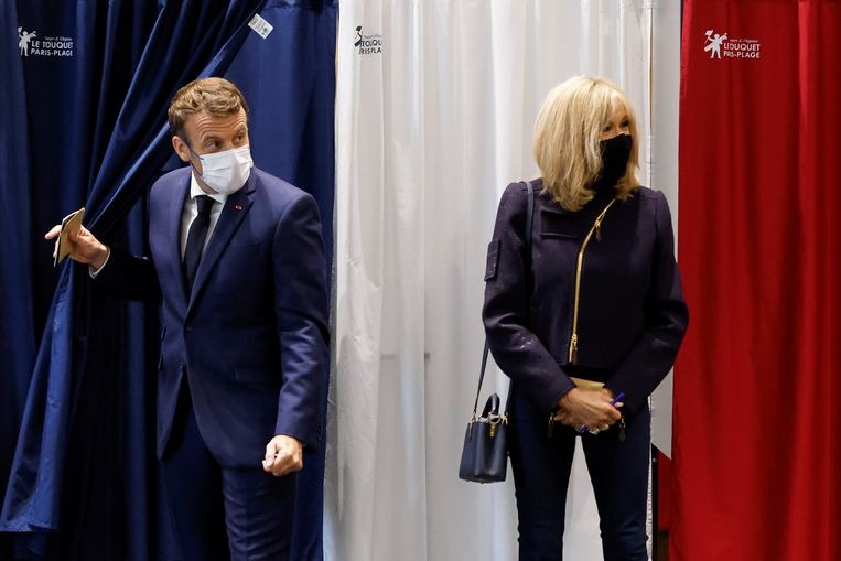 President Emmanuel Macron komt tussen de covid-gordijnen uit het stemhokje. De verkiezingen waren geen succes voor zijn partij. Rechts zijn echtgenote Brigitte.  Beeld REUTERS