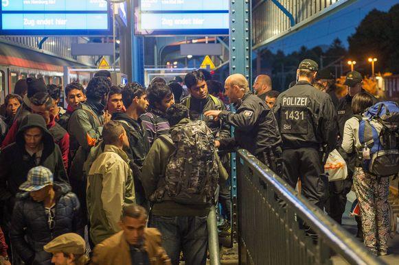 De Duitse politie informeert vluchtelingen in het station van grensstad Flensburg, gisteren.