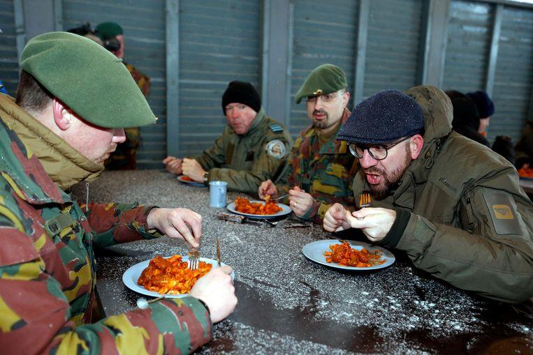 Premier Michel eet een hapje mee met de troepen in Estland, woensdag. Het doembeeld van regeringen zonder Franstalige liberalen is allicht al even moeilijk te verteren. Beeld BELGA