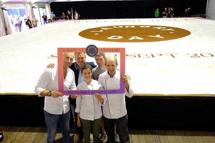 De organisatoren en de bakkers bij de enorme taart.