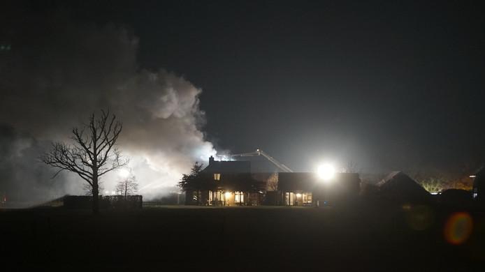 De brandweer bestrijdt de brand in het buitengebied van met groot materieel.