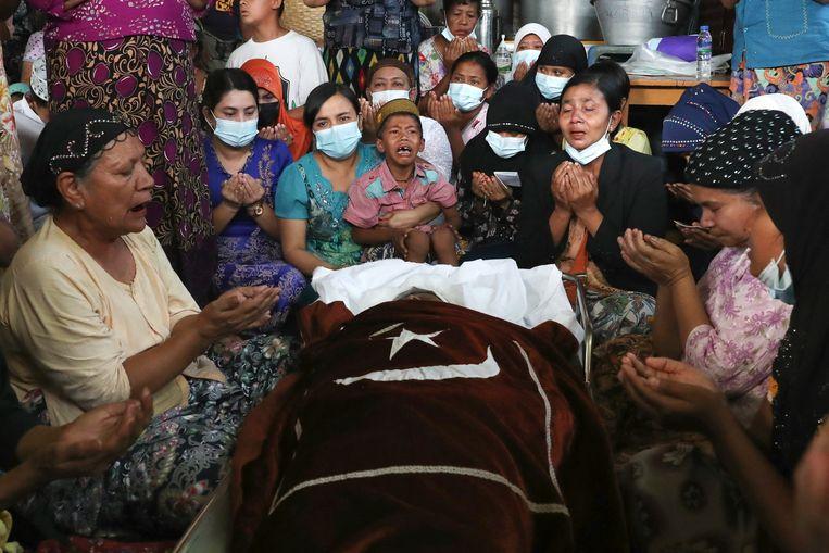Familie en vrienden bidden naast het lichaam van een Myanmarese vrouw die volgens haar naasten is vermoord door het leger. Beeld AP