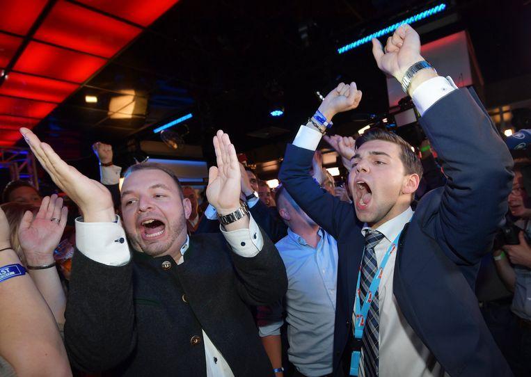 Uitgelaten AfD-aanhangers vieren de verrassend grote winst van hun partij. Beeld EPA