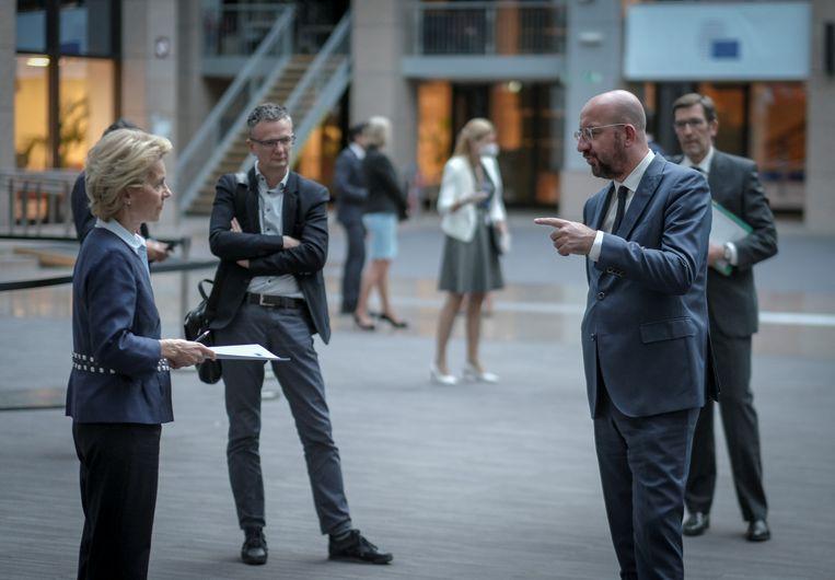 Voorzitter Charles Michel van de Europese Raad (voorgrond, rechts) praat op gepaste afstand na met voorzitter Ursula von der Leyen van de Europese Commissie (links), na afloop van hun afsluitende persconferentie over de EU-videotop.  Beeld REUTERS
