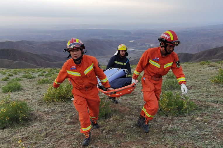 Reddingswerkers dragen apparatuur op een brancard in de zoektocht naar gewonde hardlopers. STR / AFP Beeld Hollandse Hoogte / AFP