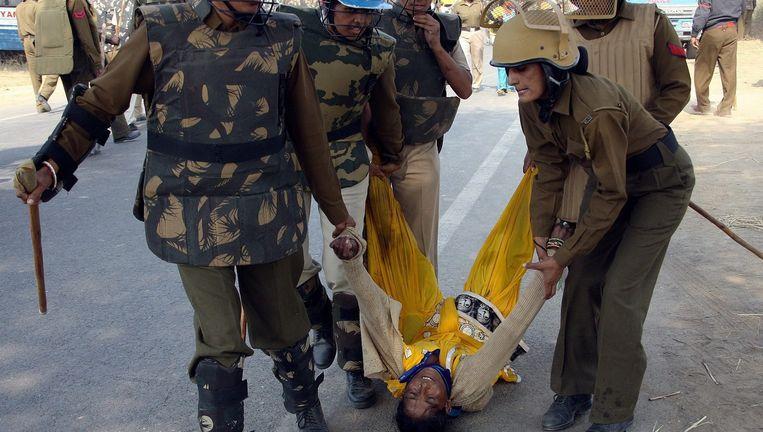 Een demonstrant wordt weggesleept door de politie. Beeld EPA