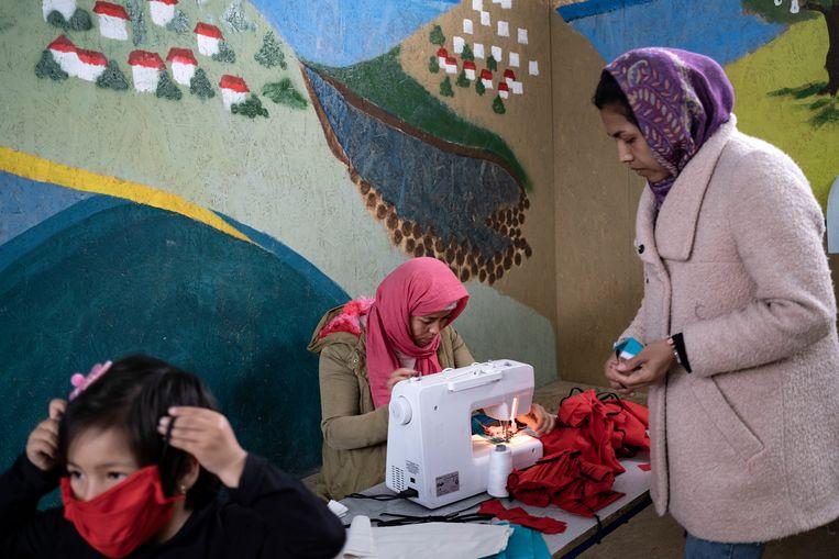 Migranten op Lesbos zijn zelf begonnen met het maken van mondkapjes om het virus tegen te gaan. Beeld AP