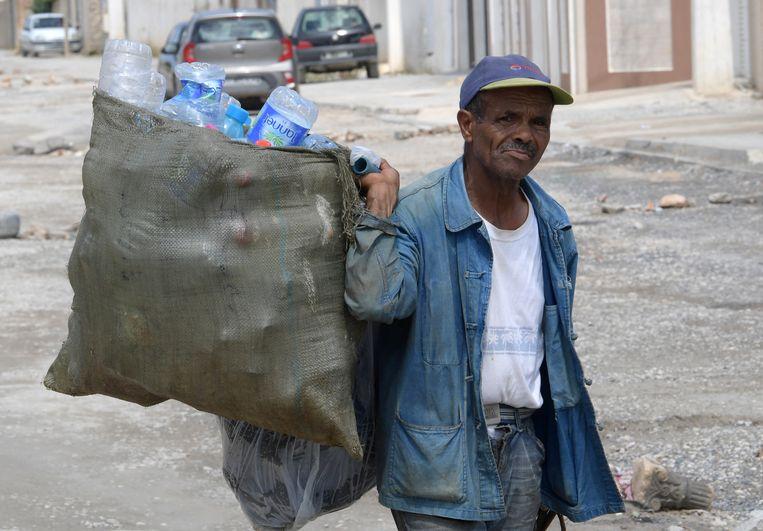 Een man verzamelt afval voor hergebruik in Tunis, de hoofdstad van Tunesië. Beeld Hollandse Hoogte / AFP