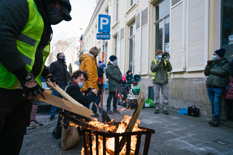 Actievoerders warmen zich aan een vuurkorf. 'Nooit hebben we als wijk meer aan elkaar gehangen.' Beeld Wouter Van Vooren