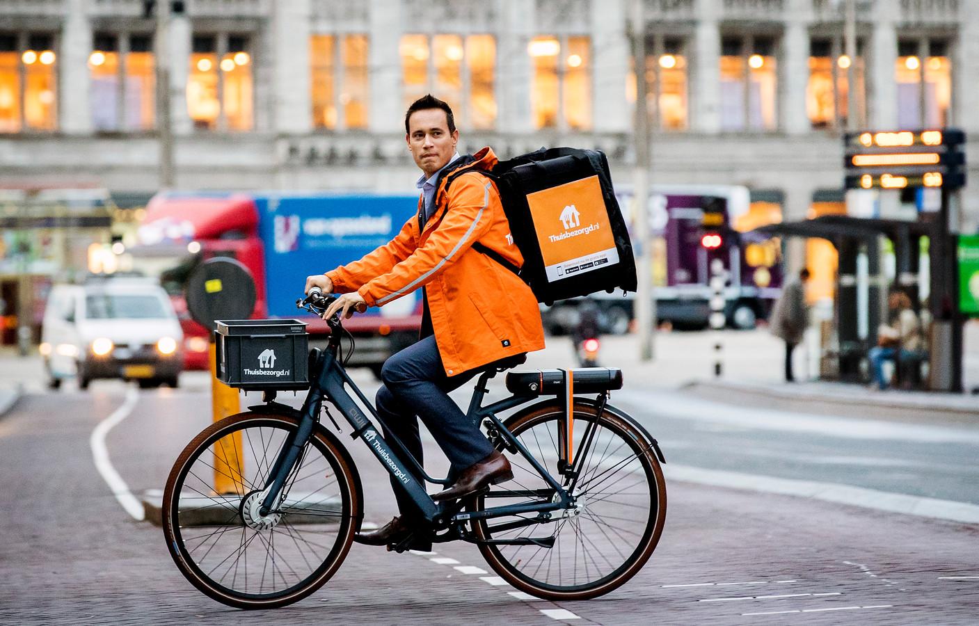 CEO Jitse Groen van Takeaway komt op de fiets aan bij Beursplein 5 voor de beursgang van het bedrijf.