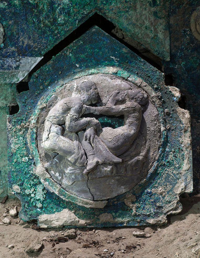Een detail van de opgegraven ceremoniële Romeinse pronkwagen, die deels gemaakt is van ijzer met versieringen van brons.   De wagen werd ontdekt in een veranda voor een stal waar, al in 2018, de overblijfselen van 3 paardachtigen, waaronder een getuigd paard, waren gevonden. Beeld AP