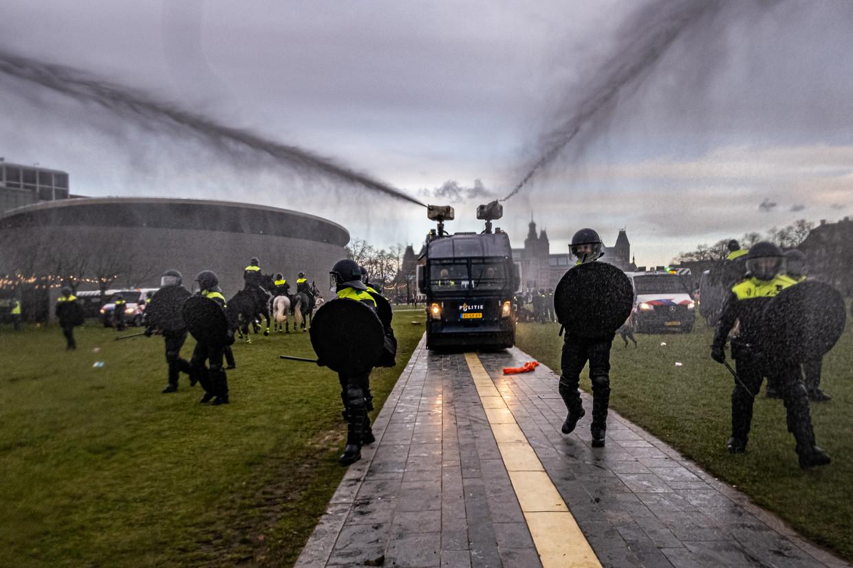 De waterwerpers spuiten aanvankelijk over de hoofden heen, in de hoop dat mensen met een nat pak wegvluchten. Beeld Joris van Gennip