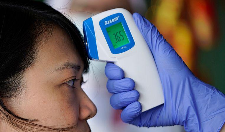 De temperatuur van een bezoeker wordt gecheckt in verband met het coronavirus.  Beeld AP