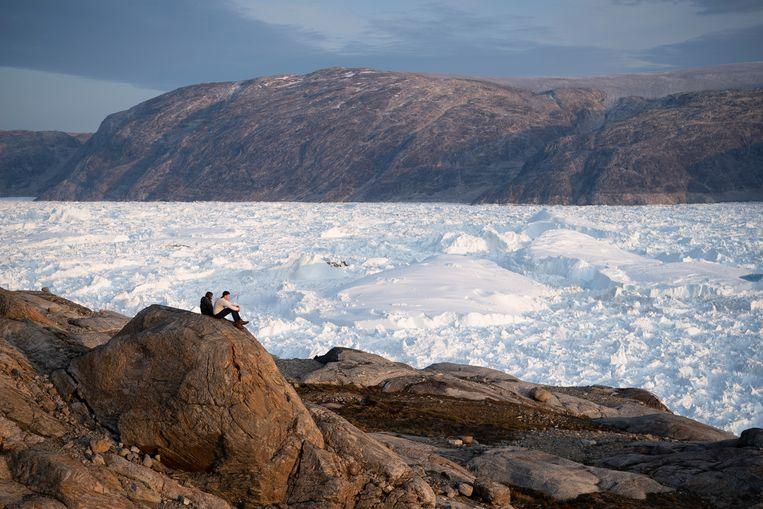 Onderzoekers bij de Helheim-gletsjer op Groenland. Sinds 2005 werd de gletsjer tien kilometer korter. Beeld AP