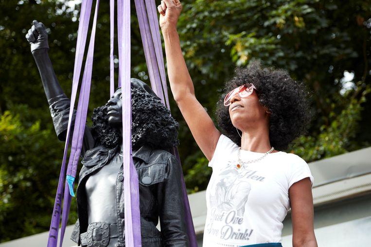 Demonstrante Jen Reid poseert naast haar standbeeld vlak voor het wordt weg gehaald.  Beeld MARC QUINN STUDIO via REUTERS