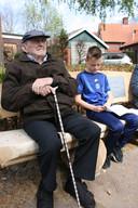 De 100-jarige Jack Koeken op het bankje dat hij van de gemeente Rucphen kreeg. Naast hem de 9-jarige Tim.