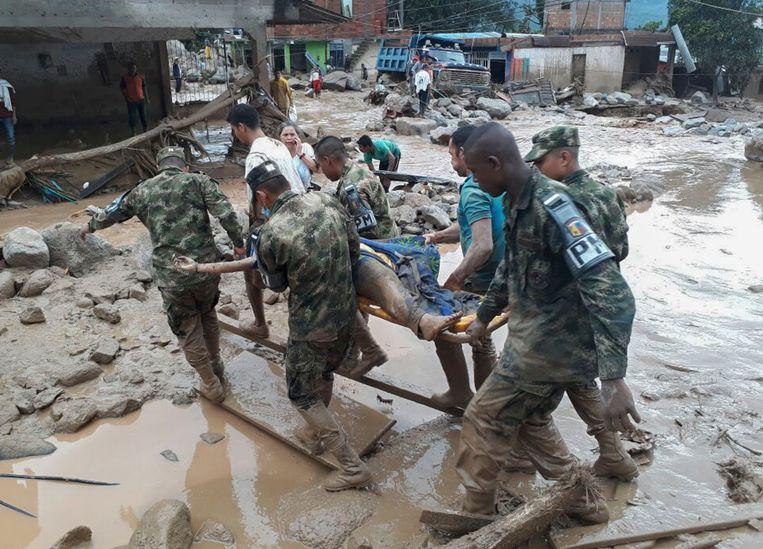 Soldaten in Mocoa dragen het lichaam van een slachtoffer die om het leven kwam bij de overstroming. Beeld AFP