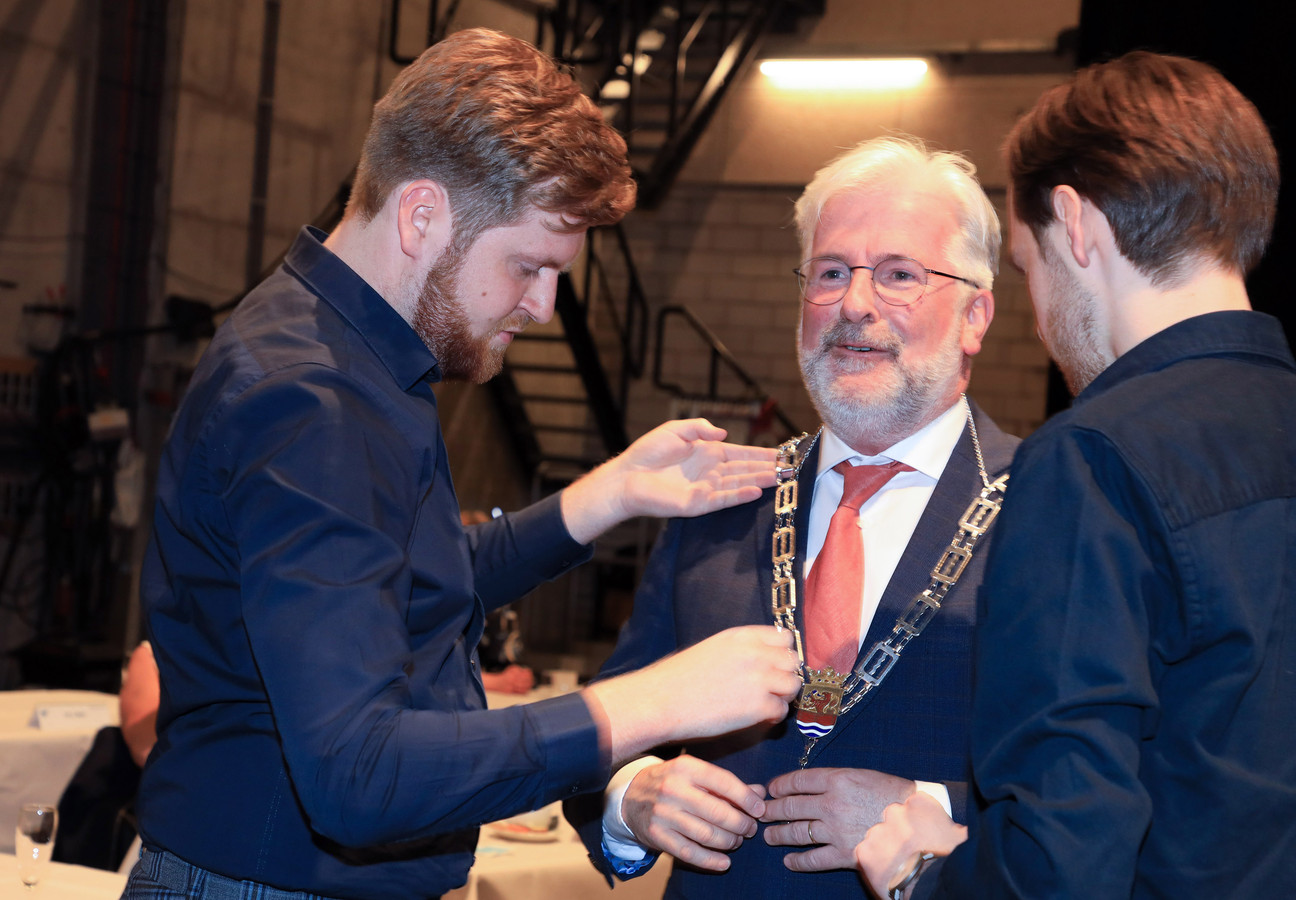 Erik van Merrienboer krijgt de Terneuzense ambtsketen omgehangen door zijn zoons Merijn (23) (links) en Diederik (19).