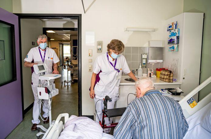 Kees de Ruijter en Loes den Ouden op de kamer van patiënt Willem Zwiers, die maar wat blij is met de aandacht die hij krijgt van de zorgreservisten. ,,Een dag duurt anders heel lang.''