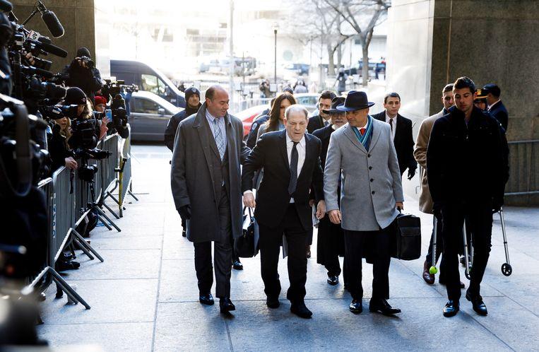 Harvey Weinstein wordt omringd door mannen die uit de jaren vijftig lijken te komen. Beeld EPA