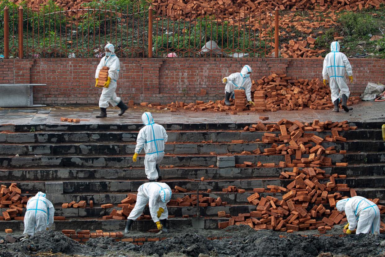 Nepalese werknemers in beschermende pakken breiden een crematorium uit in hoofdstad Kathmandu. Het land ziet het aantal doden door de coronacrisis toenemen.  Beeld EPA