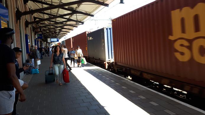 Passagiers bij spoor 1 op het station Dordrecht, terwijl een goederentrein voorbij dendert.