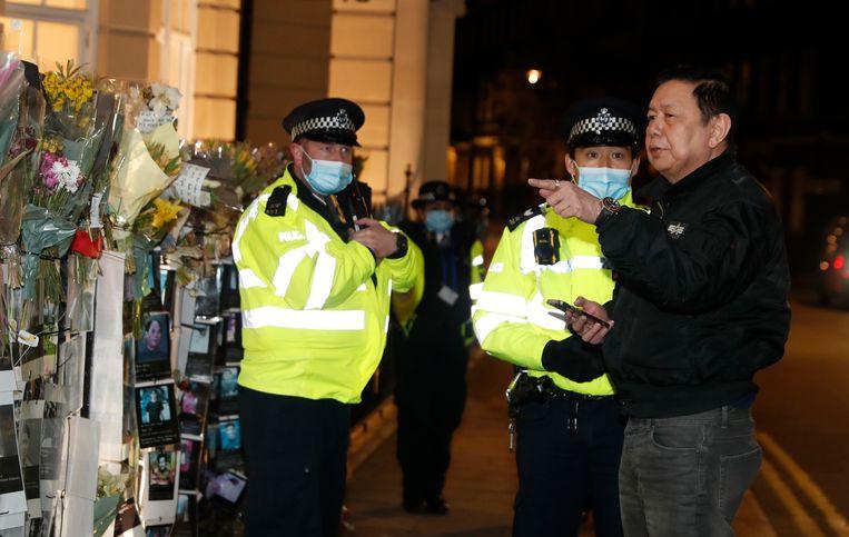 De ambassadeur van Myanmar in het Verenigd Koninkrijk praat met agenten buiten het ambassadegebouw. Beeld AP