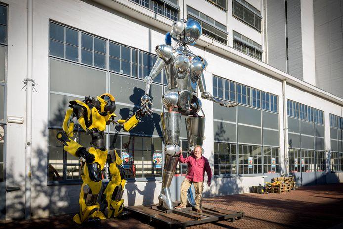 René Paré met de enorme robots van Jelle de Graaf voor het Klokgebouw, waar het makersfestival plaatsvindt.