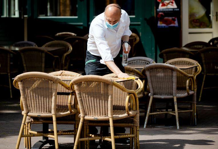 Een medewerker van een café desinfecteert een terras op het Rembrandtplein in Amsterdam. Beeld HH