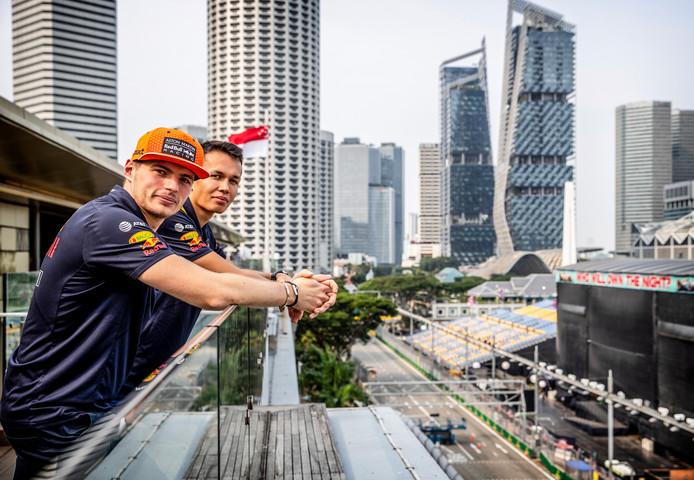 Max Verstappen kijkt met zijn Red Bull-collega Alexander Albon uit over het circuit in Singapore, met rechts het muziekpodium.